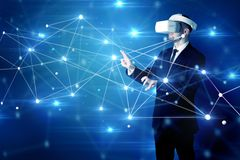 Man touching 3D connectivity and network signs. Businessman in virtual reality goggles investigate global network connectivity concept royalty free stock photo