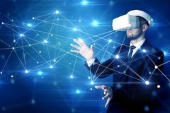 Man touching 3D connectivity and network signs. Businessman in virtual reality goggles investigate global network connectivity conceptn stock photography