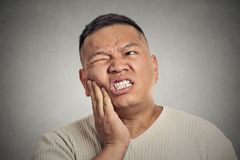 Man touching face having bad pain, tooth ache. Closeup portrait headshot middle aged man touching face having bad pain, tooth ache, isolated grey wall background royalty free stock photography