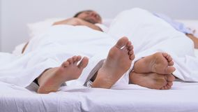 Man touching feet of angry woman, quarrel in bed in morning, problem in marriage. Stock footage stock footage