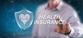 Man touching a health insurance concept. On a touch screen with his finger royalty free stock image