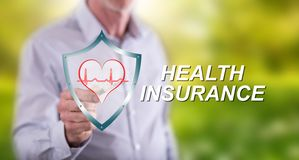 Man touching a health insurance concept. On a touch screen with a pen royalty free stock photos