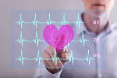 Man touching a heart beats graph concept on a touch screen. With his finger Royalty Free Stock Photos