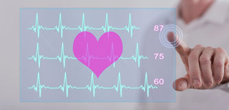 Man touching a heart beats graph concept on a touch screen. With his finger Stock Image