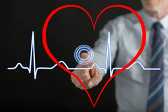 Man touching a heart beats graph on a touch screen Royalty Free Stock Photos