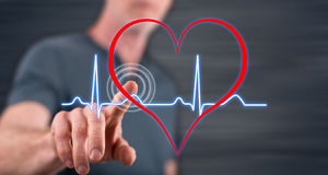 Man touching a heart beats graph on a touch screen. With his finger Stock Photos