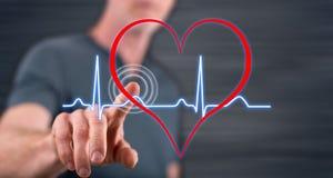 Man touching a heart beats graph on a touch screen Stock Photos