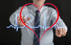Man touching a heart beats graph on a touch screen. With his fingers Stock Photo