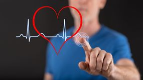 Man touching a heart beats graph on a touch screen. With his finger Royalty Free Stock Images