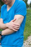 Man touching his arm. Arm ache royalty free stock image