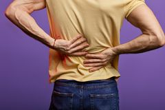 Man touching his back, guy has disk peoblems in his back stock images