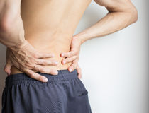 Man touching his back because of severe back pain. Athletic young man, lower back pain Royalty Free Stock Photo