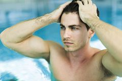Man touching his hair in the swimming pool. By raising his hand Royalty Free Stock Image