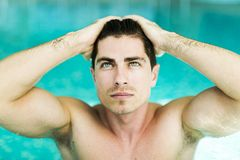Man touching his hair in the swimming pool. By raising his hand Royalty Free Stock Photos