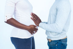 Man touching his pregnant wife belly while standing Royalty Free Stock Image