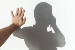 Man touching his shadow on white wall Royalty Free Stock Image