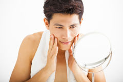 Man touching his smooth face after shaving. Young  man touching his smooth face after shaving Royalty Free Stock Images