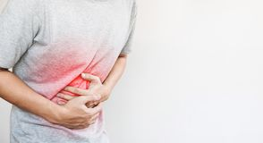 A man touching his stomach, red highlight concept of stomach pain and others stomach disease. A man touching his stomach , red highlight concept of stomach pain stock photo