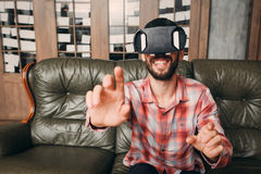 Man touching invisible keyboard in vr glasses. Young male in virtual reality headset touching objects in interactive environment, free space Stock Photography