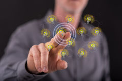 Man touching light bulbs on a touch screen. With his finger Royalty Free Stock Photography