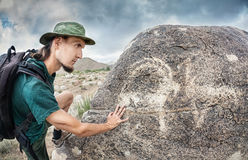 Man touching petroglyph with goat Stock Photos