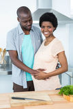 Man touching pregnant womans stomach in kitchen Royalty Free Stock Image