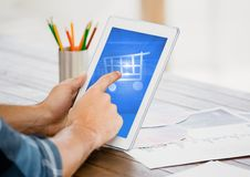 Man touching shopping cart icon on digital tablet royalty free stock photos