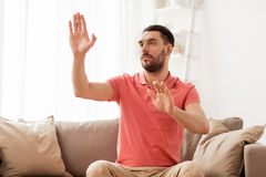 Man touching something imaginary at home Stock Photos