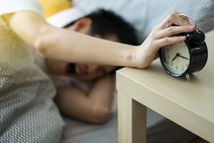 A man touching to turn it off alarm clock. Alarm clock not working in morning concept stock photography