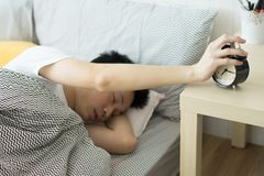 A man touching to turn it off alarm clock. Wake up early after work concept stock photography