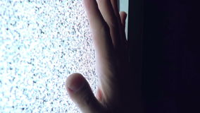 Man Touching TV Screen with Static Noise in Dark Room. Adult Caucasian Man Touching TV Screen with Static Noise in Dark Room Late at Night after the Television stock video