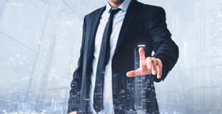 Man touching virtual screen,  modern skyline hologram - real estate business concept royalty free stock image