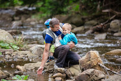 Man touching water in mountainous river while carrying his son in wrap sling Stock Image