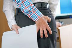 Man touching woman`s butt. Hand Sexually Harassing Boss hugs his woman subordinate in office By Touching Her Ass. Sexual harassment at work. Man touching woman`s royalty free stock photos