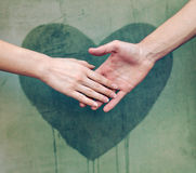 Man touching woman's hand. With a heart painted wall in background royalty free stock image