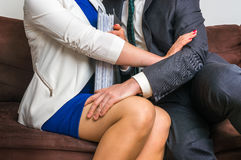 Man touching woman`s knee - sexual harassment in office. Man touching woman`s knee - sexual harassment in business office