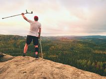 Man tourist after accident use knee brace features and forearm crutches. Man looking over. Valley to Sun hang at horizon stock photography