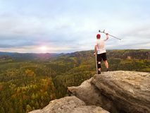 Man tourist after accident use knee brace features and forearm crutches. Man looking over. Valley to Sun hang at horizon stock image