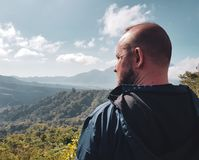 Man tourist admire beautiful mountain view in Bali. Back view of man tourist admire beautiful view of Batur lake and Mount Agung in Bali, Indonesia stock photography