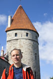 The man, tourist on a  background of an ancient tower of a city wall. Tallinn, Estonia. Stock Photos
