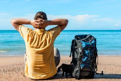 Man tourist with a backpack looking at the beautiful calm sea on. Vacation Stock Images