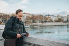 Man tourist with backpack and map. Admiring Rhone river from Bonaparte Bridge, Lyon, France Stock Image