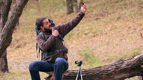 Man tourist with a backpack. Selfie in the forest. stock footage