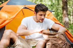 Man tourist with backpack at touristic tent in forest. Handsome young man tourist with backpack at touristic tent in forest Royalty Free Stock Images