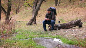 Man tourist with a backpack uses smartphone in the forest