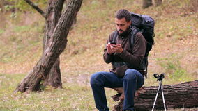 Man tourist with a backpack uses smartphone in the forest stock video footage