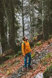 Man tourist with backpack walking alone in autumn forest stock photography