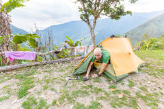 Man tourist backpacker awakening getting out tent camping, Boliv Stock Photography
