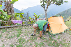 Man tourist backpacker awakening getting out tent camping, Boliv Stock Images