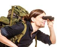 Man tourist backpacker looking through binoculars. Royalty Free Stock Images